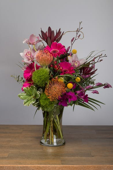 Vase with vibrant flowers and tropical flowers