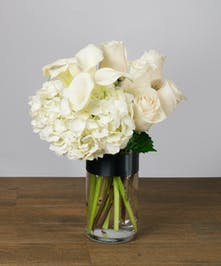 Vase of white calla lilies , roses and hydrangea