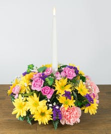 Spring Flowers in a centerpiece design with a single taper candle