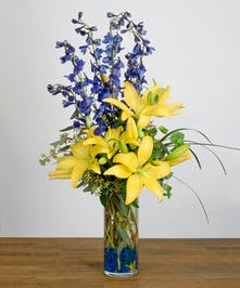 Vase with blue delphinium and yellow lilies