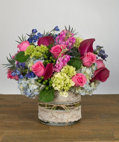 Vase with compact design of roses and calla lilies