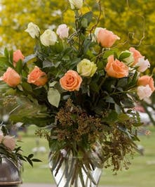 Vase filled with peach and white roses