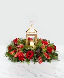 Centerpiece with red roses and greens with a gold lantern in the center