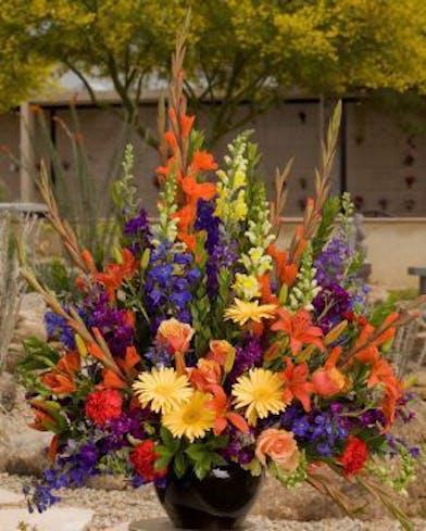 Sympathy arrangement with vibrant garden mix of flowers