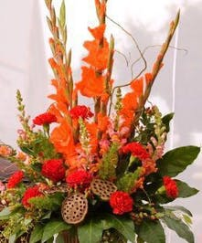 Sympathy arrangement with vibrant coral color flowers