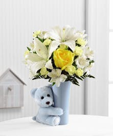 Blue vase with yellow and white flowers and a cute blue teddy bear