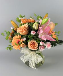 Pastel Peach and Pink Flowers in a low glass vase