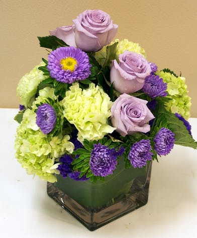Purple spring flowers in a cube vase