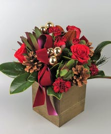 Wooden Box with red roses and red mini carnations with holiday decor and magnolia leaves