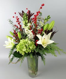 Vase with white lily, hydrangea and red berries with holiday greens