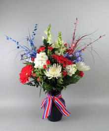 Vase of red white and blue flowers, with bow, carnations, mum, delphinium