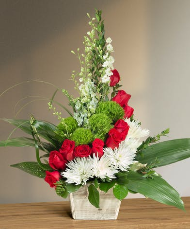 Red, white and green flowers in a funeral basket