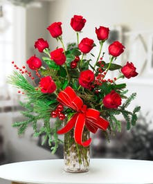 Dozen Red roses with holiday greens and decor