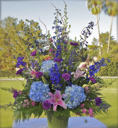 Sympathy arrangement in pink, blue and purple flowers
