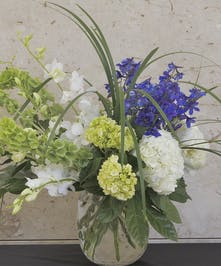 Vase of mixed flowers in green, blue and white