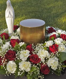 Urn Wreath with red roses, white carnations and a madonna statue