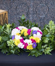 Urn display with garden mixed flowers in shape of a heart in bed of greenery
