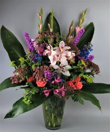 Vase with vibrant flowers and tropical orchids
