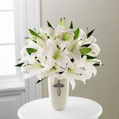 Vase with cross on it filled with white oriental lilies