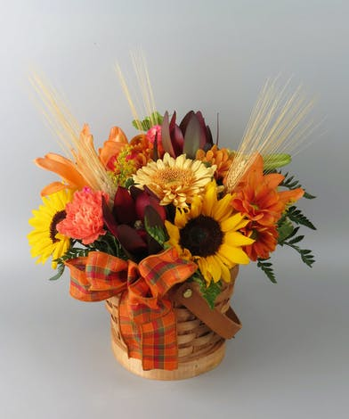 Basket of bright fall colors and flowers with daisies and sunflowers