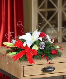 Holiday centerpiece with greens, white lily, roses, and ribbon