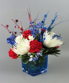 Cube vase with red white and blue flowers, carnations, mums, delphinium
