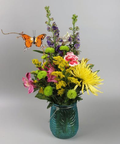 Blue vase filled with a mix of pretty wildflowers
