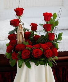 Sympathy design with all red roses and Madonna statue
