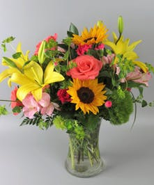 Vase of  vibrant color flowers with sunflowers, lilies, roses