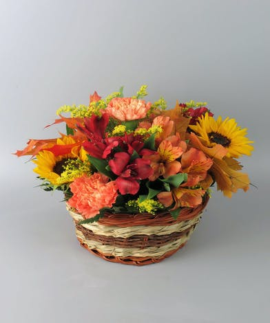 Basket of fall flowers with sunflower and alstroemeria
