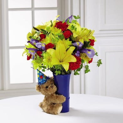 Bold flowers in a vase with a plush teddy bear