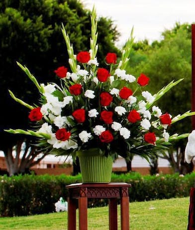 Sympathy arrangement in red and white flowers
