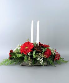 Centerpiece with candles in a log inspired container with red daises and roses