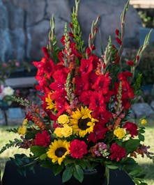 Sympathy arrangement with gladiolas, sunflowers and other bright flowers