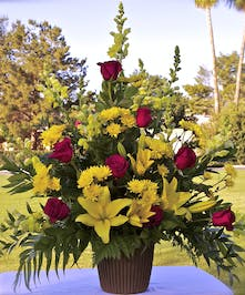 Sympathy arrangement roses and lilies in shades of reds and yellow