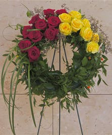 Sympathy wreath with greenery and red and yellow roses