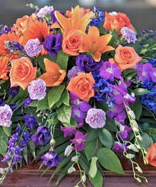 Casket Spray with vibrant bold colors, blue, orange and purple