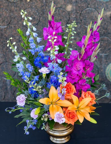 Sympathy Arrangement in vibrant orange, blue, purple flowers