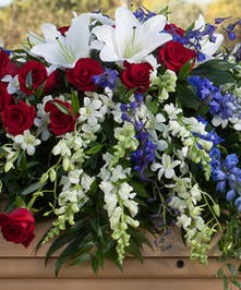 Casket Spray with red, blue and white flowers, and lilies