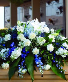 Casket Spray with blue and white flowers, and lilies