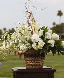 Sympathy arrangement with all white roses and white larkspur
