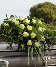 Casket Spray with greenery and green roses