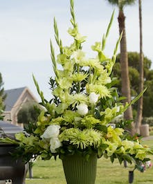 Sympathy arrangement with green tone flowers