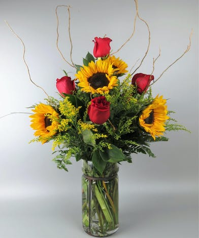 Glass Lantern style vase with sunflowers and red roses