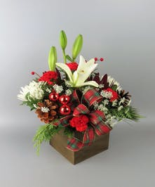 White lily and red carnations with ribbons and pinecones in a wooden box
